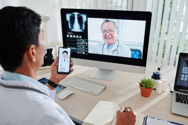 성숙한 베트남 의사가 두 동료에게 전화하여 어려운 담즙 성 폐렴 사례를 논의하는 영상