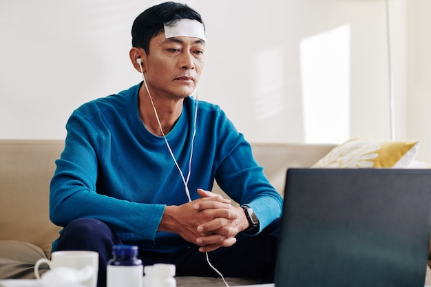 Mature vietnamese man with cooling fever patch on his forehead having online consultation with doctor