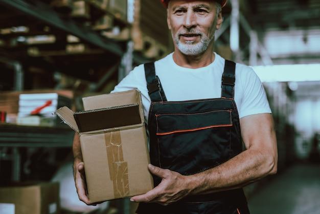 Зрелый складской рабочий держит коробку с товарами