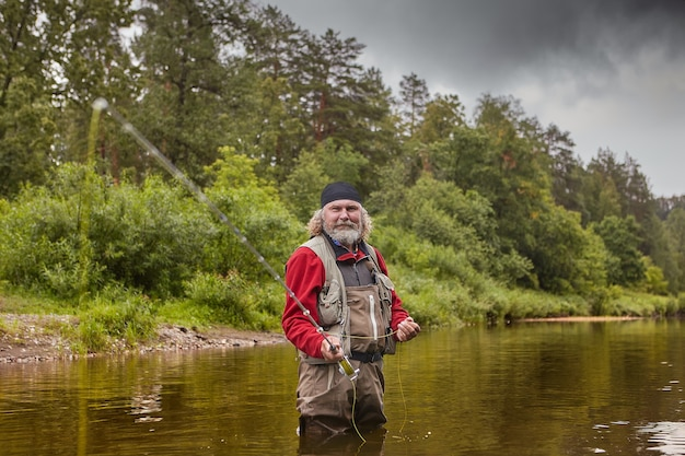 Mature white bearded man  is catching fish by fly fishing in quiet river in  forest, he wears waterproof cloth, eco-tourism.