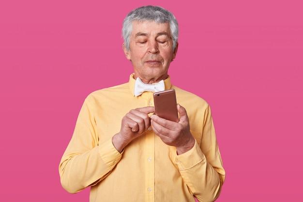 黄色のシャツと白い蝶ネクタイに身を包んだ成熟した白い髪の男の手とタイプのメッセージでスマートフォンを保持