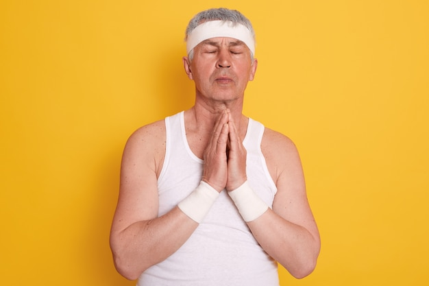 Mature white haired man wearing white t shirt and headband, keeping eyes closed, keeps hands together, praying for better life