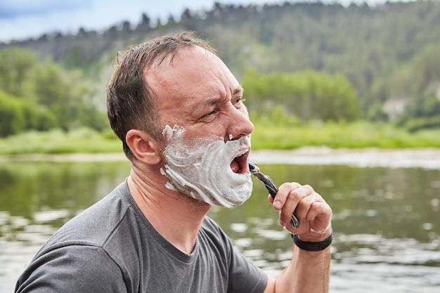 성숙한 백인 남자는 숲과 강 근처의 야생 자연에서 면도하는 동안 얼굴을 만들고, 그의 얼굴은 거품으로 덮여 있습니다.
