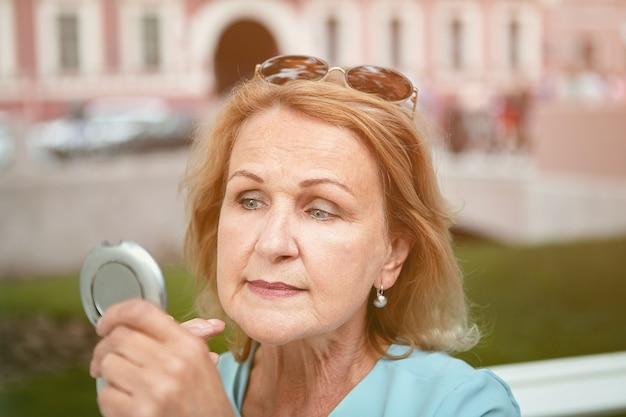 성숙한 백인 여자는 작은 둥근 거울을 사용하여 야외에서 그녀의 화장을 수정합니다.