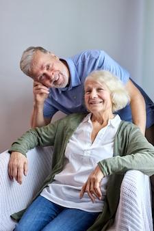成熟した妻と夫が自宅の居心地の良いソファで笑顔のカメラでポーズをとって、彼女の夫が彼女の後ろに立っている間、女性が座っています。肖像画