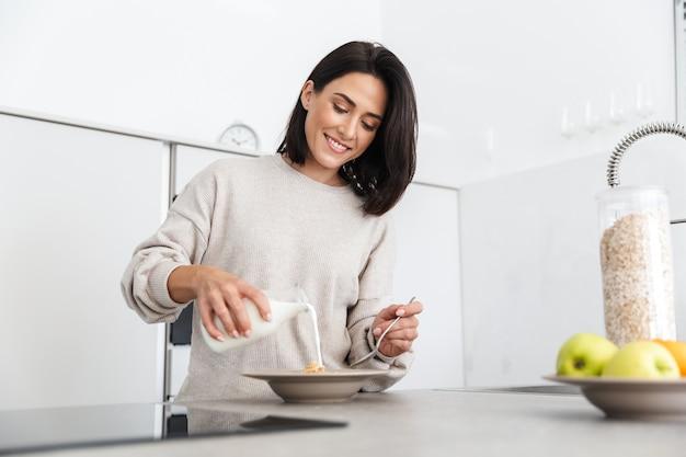 Зрелая женщина 30 лет готовит завтрак с овсянкой и фруктами, стоя на современной кухне дома
