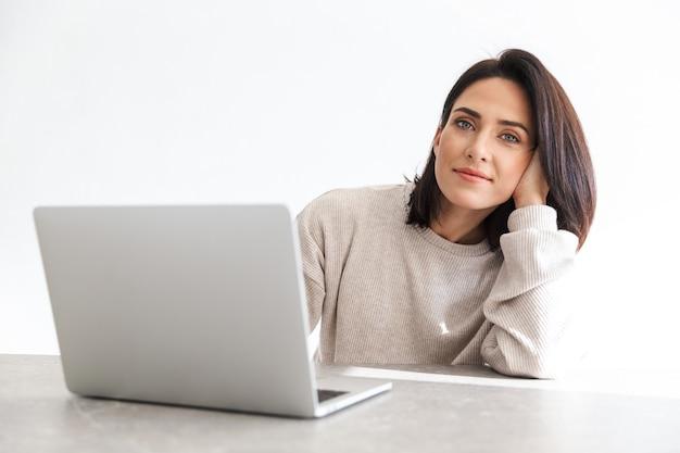 Зрелая женщина 30 лет работает на ноутбуке, сидя на белой стене в светлой комнате