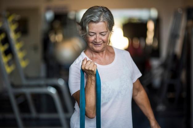 ジムで一人で成熟した女性が弾力性のあるエクササイズをしている-健康的でフィットネスのライフスタイルとコンセプト-シニアまたは年金受給者が彼女の健康的な仕事をしている