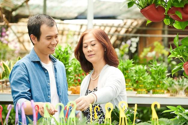 Зрелая женщина и ее взрослый сын выбирают растения и цветы в садовом центре для дома на заднем дворе