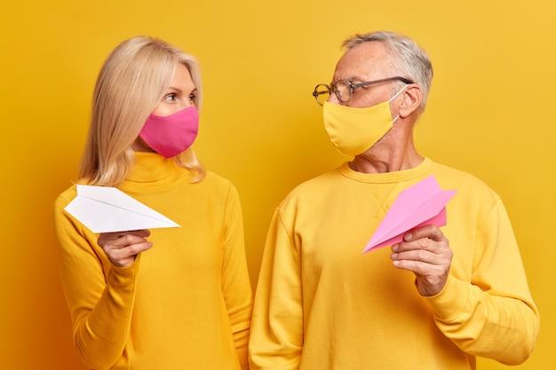 성숙한 여자와 남자는 서로를 행복하게 바라보고 수제 종이 비행기로 보호 마스크를 착용하고 노란색 벽에 고립 된 코로나 바이러스 확산을 방지하기 위해 거리를 유지하려고 노력합니다