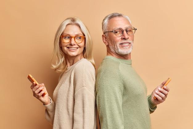 成熟した女性と男性はお互いに後ろに立って一緒に楽しんでいます茶色の壁に隔離されたインターネットをさりげなくサーフィンする服を着たソーシャルネットワークをスクロールするために電話を使用してください