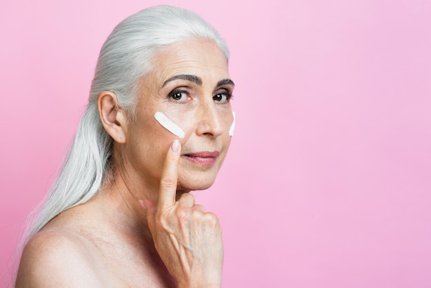 Mature woman applying cream on her face
