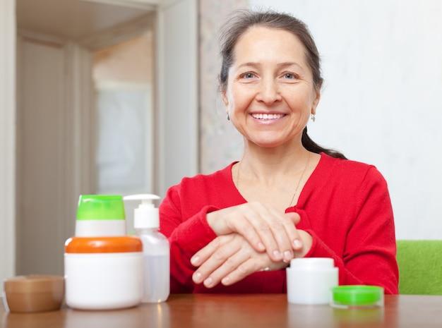 Mature woman applying cream