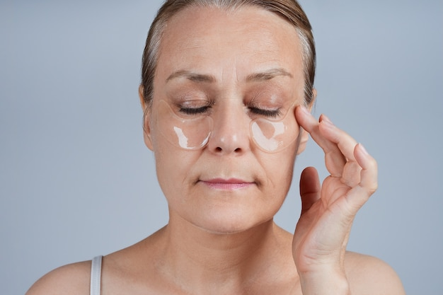 彼女の目の下にパッチを適用する成熟した女性。高齢者のスキンケアに直面します。