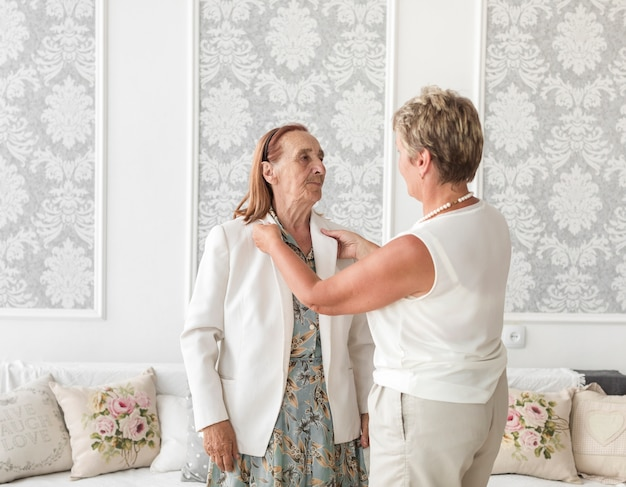 Mature woman assisting her mother wear jacket at home