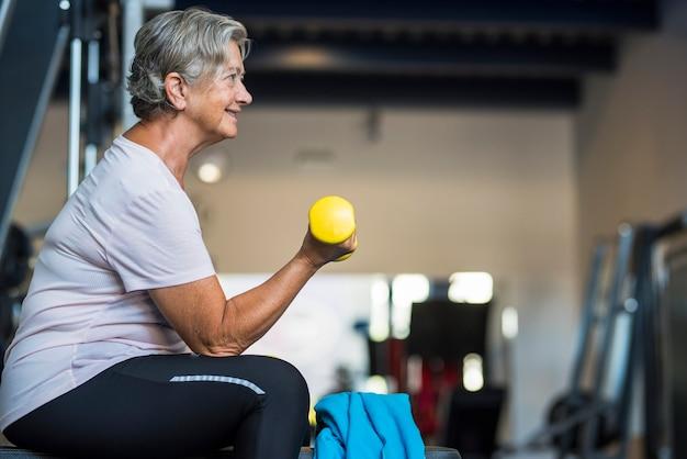 彼女の体と彼女の手にダンベルを持ってベンチに座っている彼女の上腕二頭筋を訓練しているジムの成熟した女性-健康とフィットネスのシニアライフスタイル
