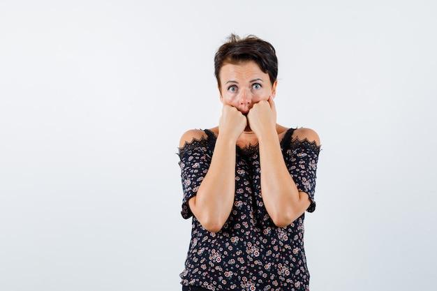 花柄のブラウス、黒いスカートで感情的に拳を噛み、興奮している成熟した女性。正面図。