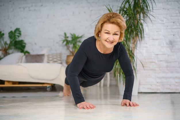 Mature woman in black sportswear doing push-ups at home against the background of a bed and a white brick wall, there are flower pots with green leaves. healthy lifestyle concept
