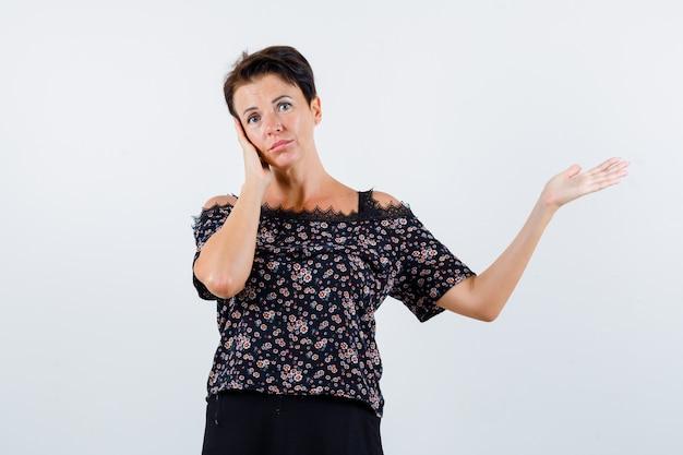 Donna matura in camicetta tenendo la mano sulla guancia fingendo di mostrare qualcosa e guardando fiducioso, vista frontale.