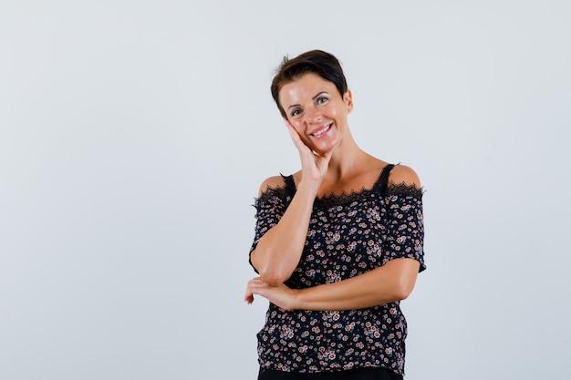 Donna matura in camicetta in posa stando in piedi e guardando allegro, vista frontale.
