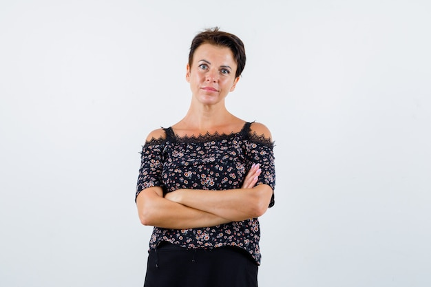 Donna matura in camicetta in piedi con le braccia incrociate e guardando fiducioso, vista frontale.