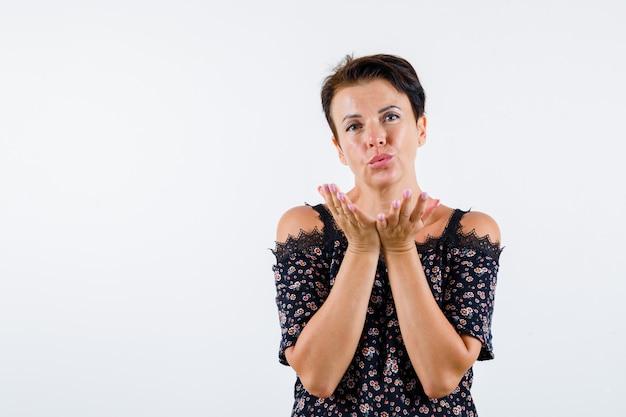 Donna matura che soffia bacio in camicetta floreale, gonna nera e affascinante. vista frontale.