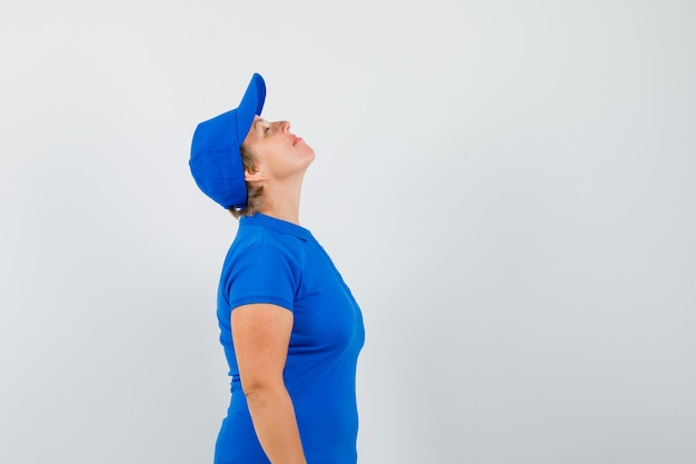 Mature woman in blue t-shirt bending head back and looking peaceful .