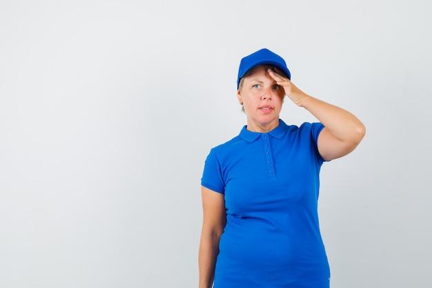 Donna matura in maglietta blu che tiene la mano sulla fronte e che sembra pensieroso.