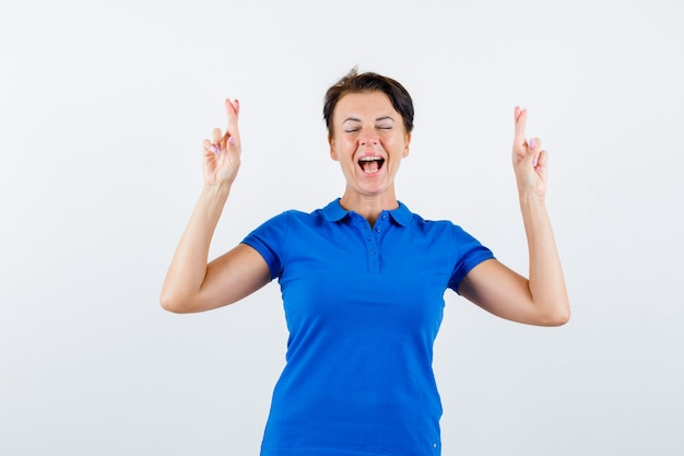 Donna matura in maglietta blu tenendo le dita incrociate e guardando fortunato, vista frontale.