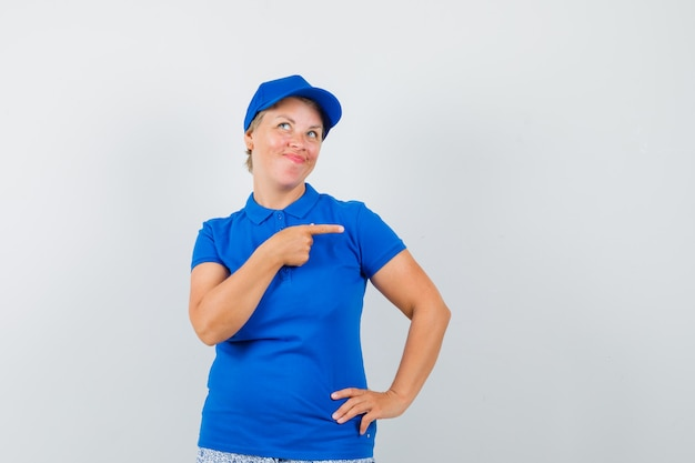 Mature woman in blue t-shirt pointing to the right side.