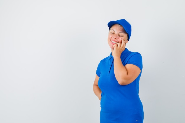 Mature woman in blue t-shirt thinking with closed eyes and looking merry