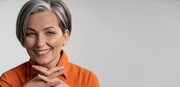 Mature woman broadly smiling with fingers crossed