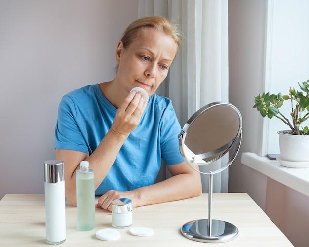 성숙한 여성은 얼굴의 노화된 피부를 돌보고 로션을 사용하여 피부를 정화합니다