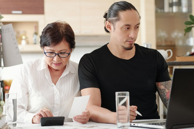 Mature woman checking receipts and making calculations when her adult son paying bills and mortgage loan payment online