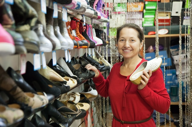 Зрелая женщина выбирает обувь