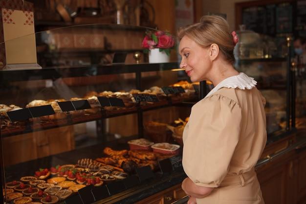 베이커리 가게에서 살 디저트를 선택하는 성숙한 여성