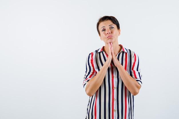 ストライプのシャツを着て祈りの位置で手を握りしめ、集中して見える成熟した女性。正面図。