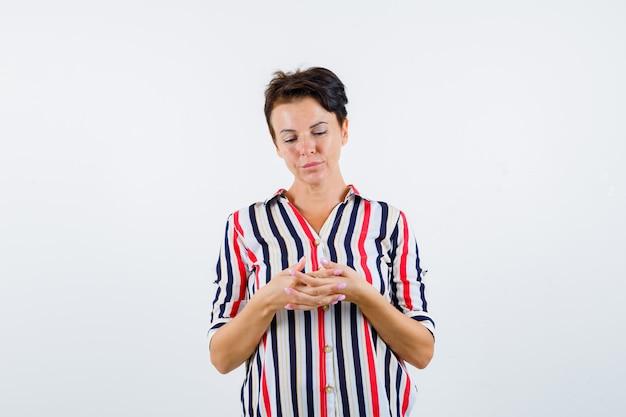 手を握りしめ、縞模様のシャツの手のひらを見て、集中して見える成熟した女性。正面図。