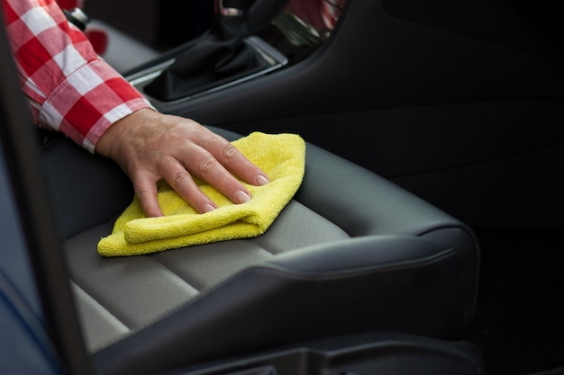 Mature woman cleaning leather seat of the car with soft yellow microfiber cloth.