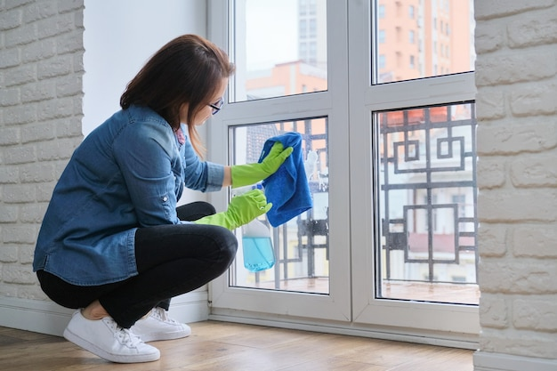 Mature woman cleaning windows at home in spring