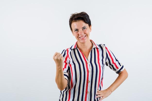 拳を握りしめ、縞模様のブラウスで腰に手をつないで、自信を持って見える成熟した女性。正面図。