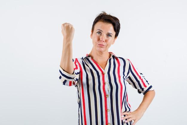 成熟した女性は拳を握りしめ、縞模様のシャツで腰に手をつないで、自信を持って、正面図。
