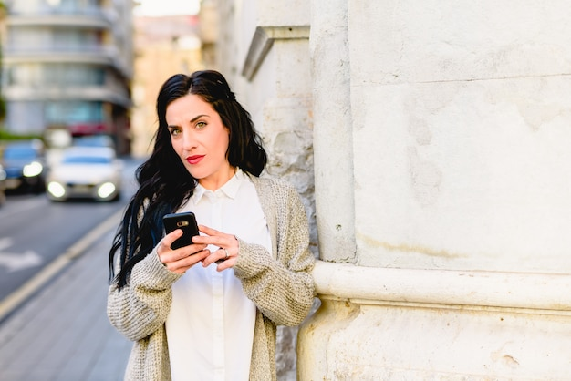 Mature woman confused and lost consulting her mobile phone.