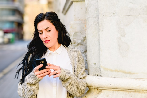 Mature woman consulting her mobile phone while visiting a city trip.