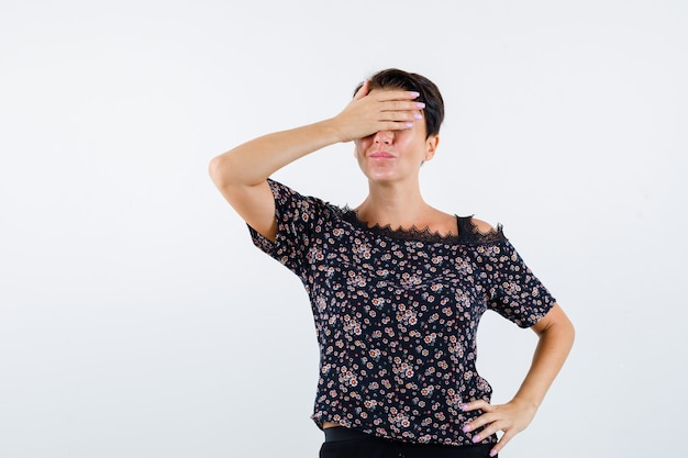 Donna matura che copre gli occhi con la mano, tenendo la mano sulla vita in camicetta floreale, gonna nera e guardando allegro, vista frontale.