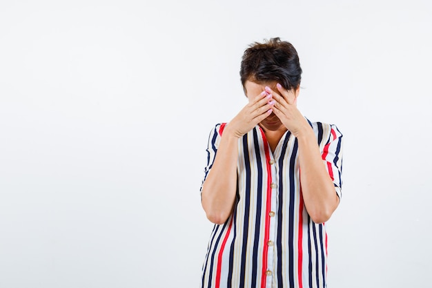 Donna matura che copre il viso con le mani in camicetta a righe e guardando tormentato, vista frontale.