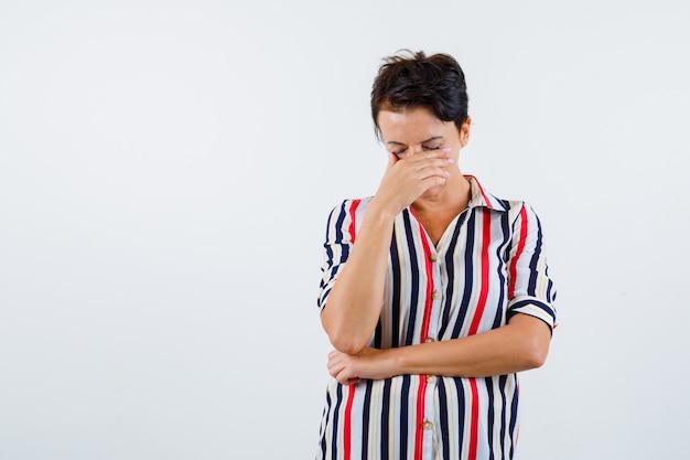 Зрелая женщина прикрыла рот рукой, держа одну руку под локтем в полосатой блузке и выглядела задумчиво. передний план. Бесплатные Фотографии