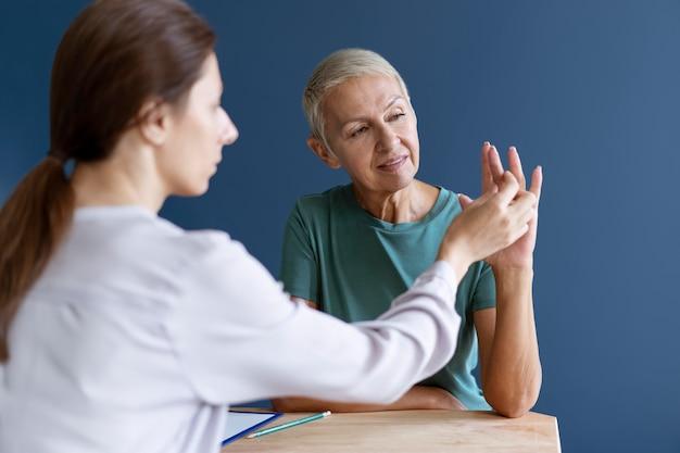 Зрелая женщина делает сеанс трудотерапии с психологом