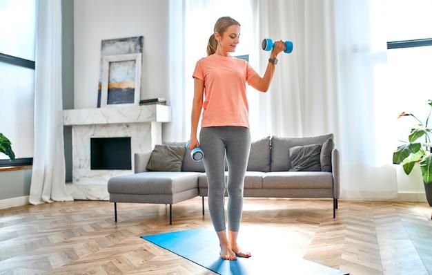 自宅でダンベルを使って運動をしている成熟した女性。
