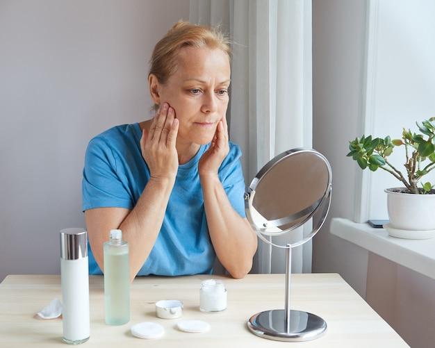 집에서 거울을 보면서 얼굴 마사지를 하는 성숙한 여성
